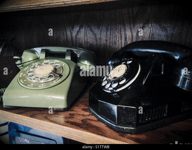 Vintage telephones in wooden bookshelf - Stock Image