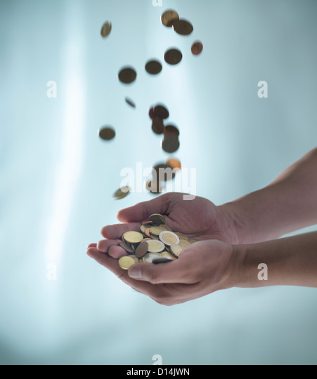 Close up of hands catching pile of coins - Stock-Bilder