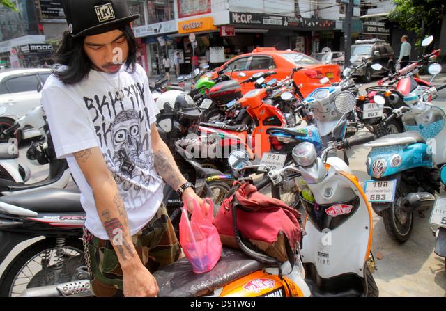 Thailand Bangkok Pathum Wan Siam Square Asian man tattoos motorcycles motor scooters - Stock Image