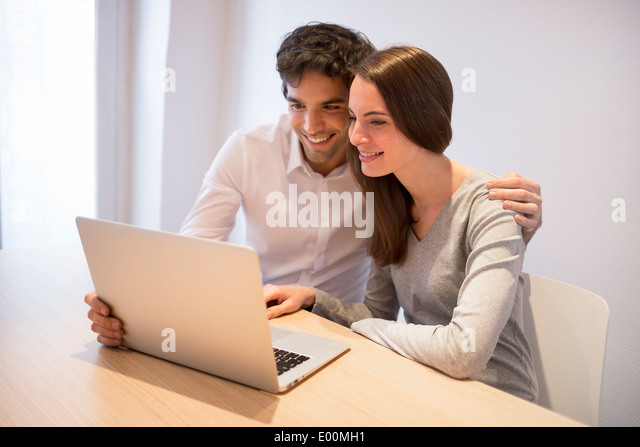 Female male happy desk computer indoors - Stock Image
