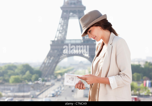 Woman reading a guide book with the Eiffel Tower in the background, Paris, Ile-de-France, France - Stock Image