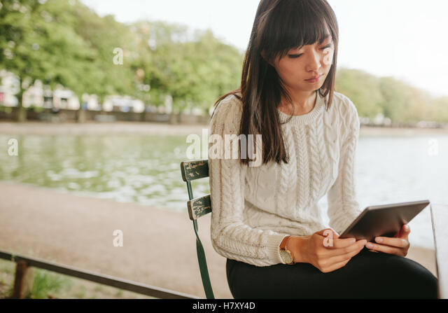 Shot of chinese woman sitting on chair by the pond and using digital tablet. Female at outdoor cafe with touch pad - Stock Image