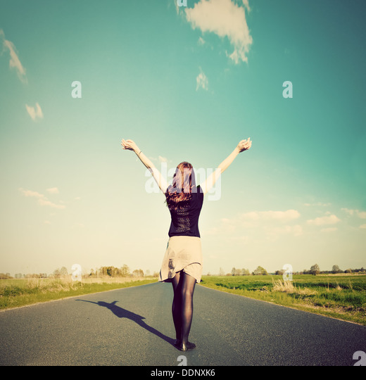 Happy woman standing with hands up on straight road facing sun. Future / freedom / hope / success concept - Stock-Bilder