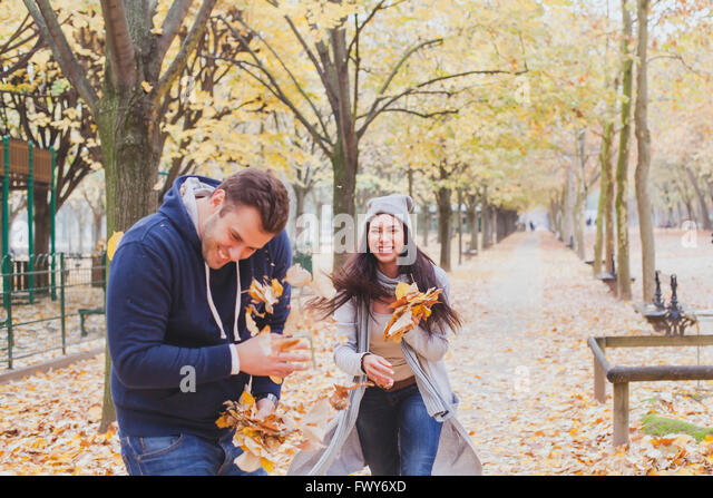 happy young couple playing and laughing together in autumn park - Stock Image