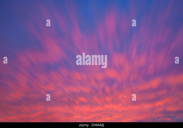Movement Of The Clouds During This Long Exposure Resemble Tongues Of Fire In This Blazing Sunset Sky Over Southwestern - Stock Image
