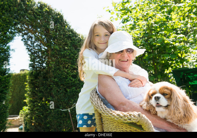 Portrait of grandmother and granddaughter with dog - Stock-Bilder