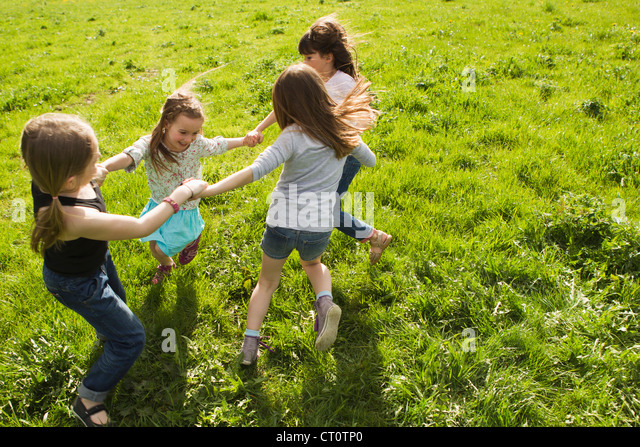 Girls playing in circle outdoors - Stock Image