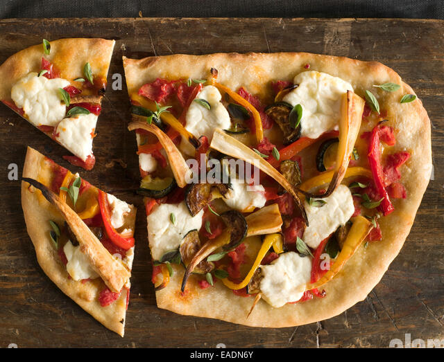 Pizza with mixed vegetables on cutting board - Stock Image