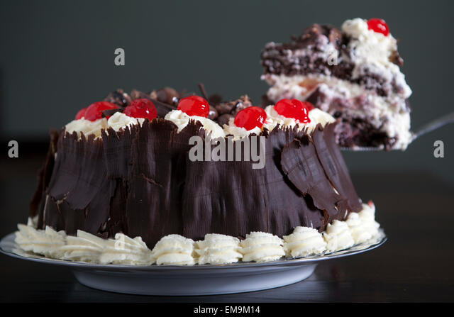 Chocolate cake with cream and cherries, being served. - Stock Image