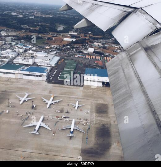 Aerial view of airplane wing, warehouses and airplanes on the ground at Narita International Airport in Chiba Prefecture, - Stock Image
