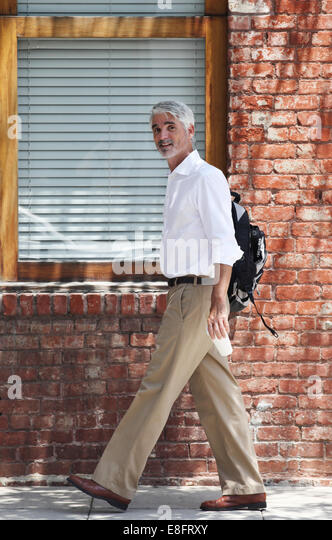 Businessman walking past building - Stock-Bilder