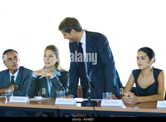 Businesspeople in committee meeting, one man standing - Stock Image