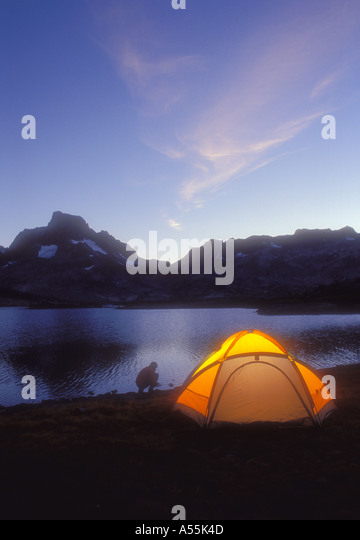 Tent and camper beside alpine mountain lake in California Model Released Photo - Stock Image