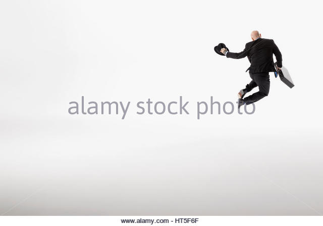 Playful businessman with briefcase jumping, clicking heels against white background - Stock-Bilder