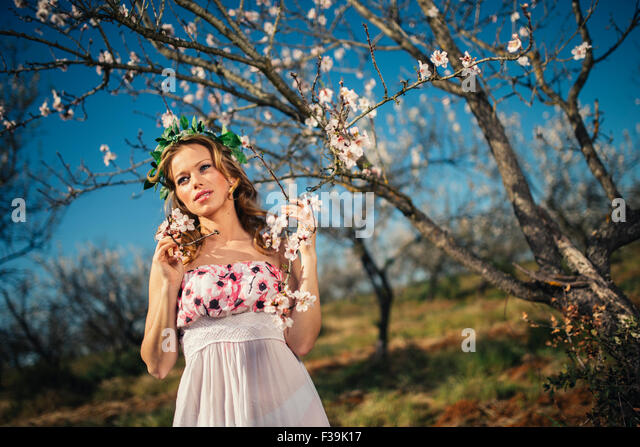 Portrait of a woman wearing a headdress standing next to a blossom tree in spring - Stock Image