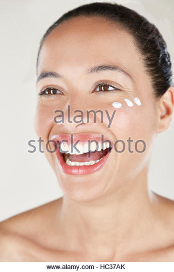 Woman with face cream on cheek, laughing. - Stock Image