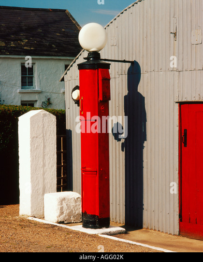 An old style service station in rurual Ireland with a red service stop beside the grey garage - Stock Image