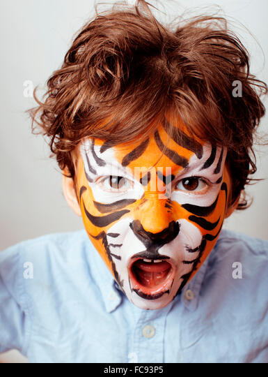 little cute boy with faceart on birthday party close up, little cute tiger - Stock Image