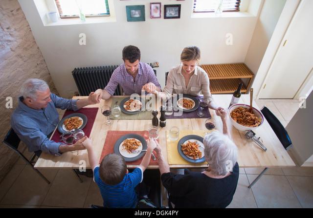 Three generation family holding hands at dinner table - Stock-Bilder