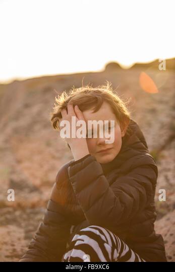 Sweden, Bohuslan, Sad boy (12-13) sitting outside at sunset - Stock Image