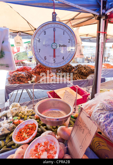 An analog dial scale at an outdoor market - Stock Image