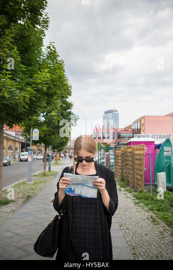 Germany, Berlin, Young woman with city map - Stock Image