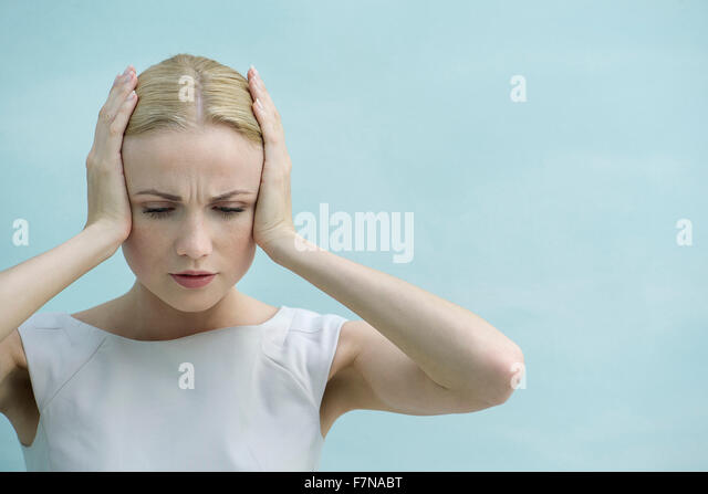 Woman holding hands over ears, looking down with furrowed brow - Stock Image