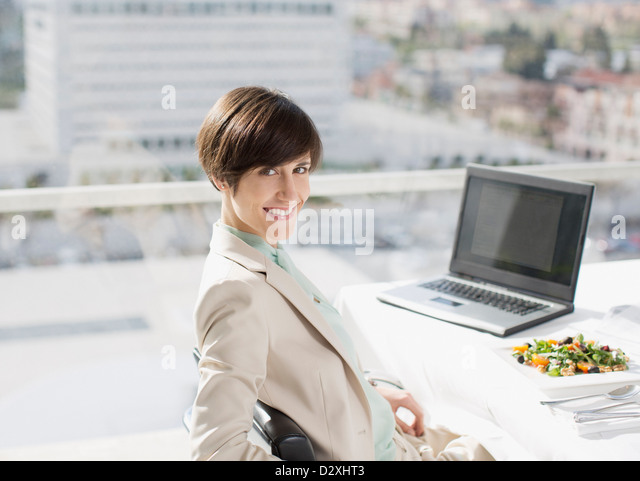 Portrait of smiling businesswoman with lunch at desk - Stock Image