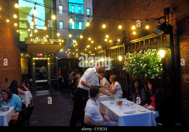 Boston Massachusetts Cambridge Harvard Square Russell House Tavern restaurant alfresco dining waiter tables night - Stock Image
