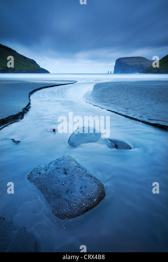 A stream runs into the sea at Tjornuvik on the island of Streymoy in the Faroe Islands. Spring (June) 2012. - Stock Image