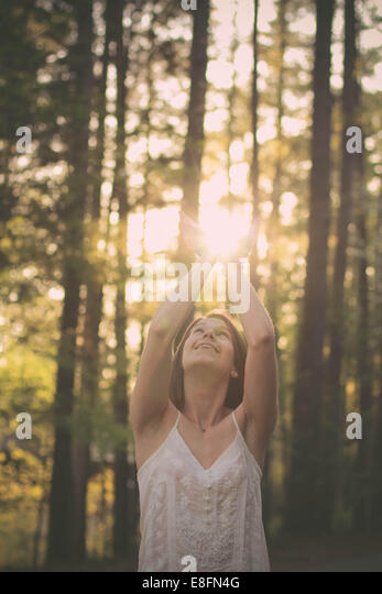 Portrait of a woman standing in forest catching sunlight in her hands, Mississippi, America, USA - Stock Image