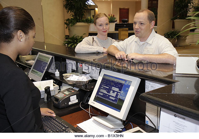 Little Rock Arkansas The Peabody Little Rock hotel lobby Black woman women man couple work job staff front desk - Stock Image