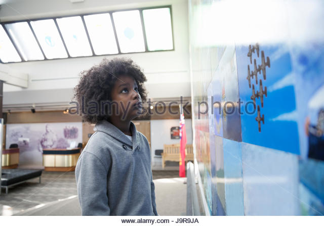 Curious African American boy student looking up at exhibit photographs in war museum - Stock-Bilder