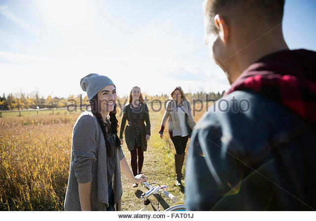 Friends with bicycle walking in sunny autumn field - Stock Image