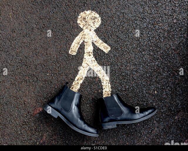 White pedestrian path marking with boots on - Stock-Bilder