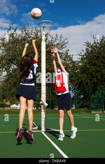 Two schoolgirls playing netball - Stock Image