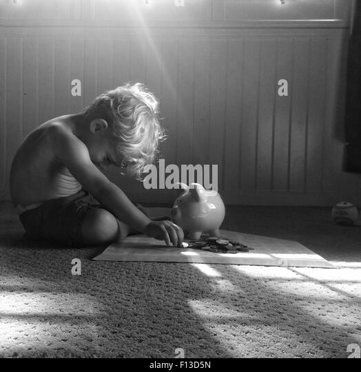 Toddler sitting on floor counting money - Stock Image
