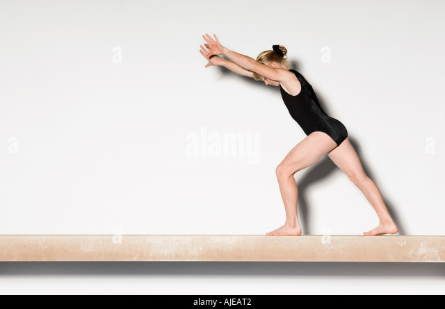Gymnast(13-15)  on balance beam preparing to do handstand, side view - Stock Image