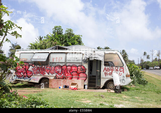 Food truck covered in graffiti parked on the side of the road in Hawaii. - Stock Image