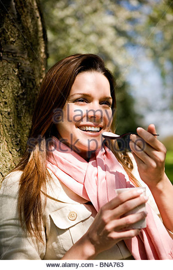 A young woman eating a yogurt, outdoors - Stock Image