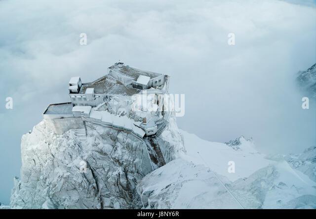 Snow covered building on cliff - Stock-Bilder