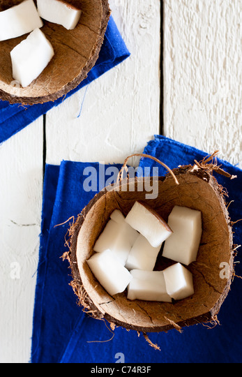 Coconut Pieces in a Shell, with Blue Napkin on White Wood - Stock Image