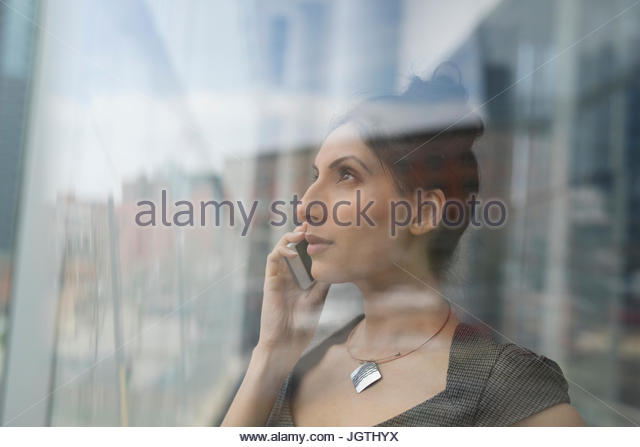 Pensive businesswoman talking on cell phone at office window - Stock Image
