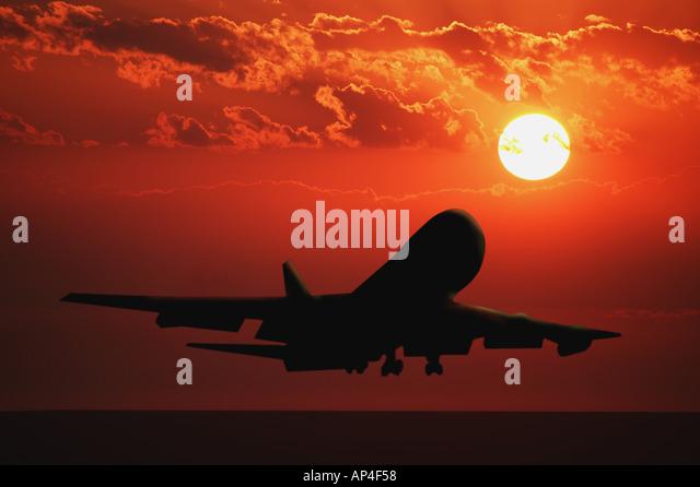 Airplane landing at sunset - Stock Image