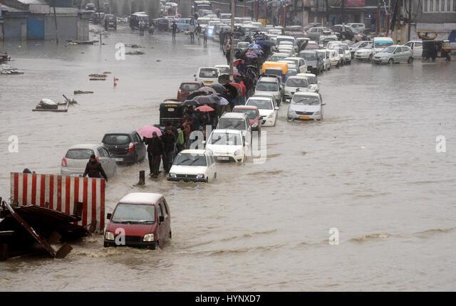 Srinagar, Kashmir. 6th Apr, 2017.  Vehicles navigate their way through a water logged street as pedestrians walk - Stock Image