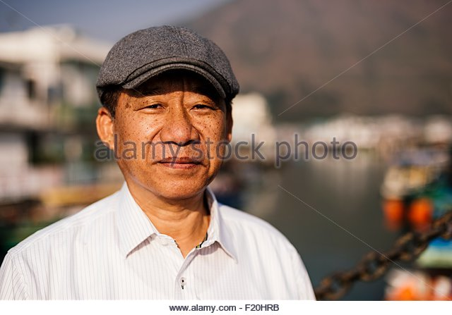 Portrait of senior man wearing white shirt and flat cap, looking at camera smiling - Stock Image