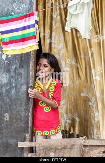 India Asian Mumbai Dharavi Shahu Nagar Road slum low income poor poverty girl home window calling - Stock Image