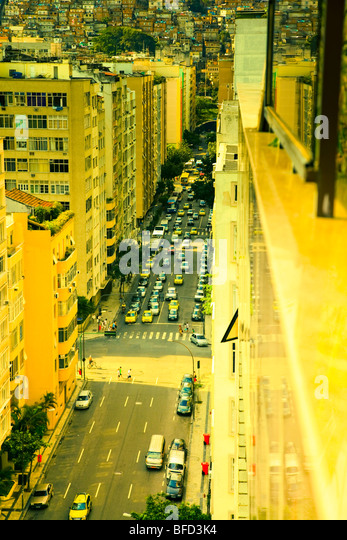 Yellow lit streetscape in Copacabana showing the close proximity to the slums or favela. Rich and poor lives side - Stock Image