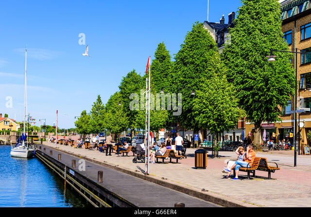 Vastervik, Sweden - June 19, 2016: People walking and resting along the seaside promenade. Real people in everyday - Stock-Bilder