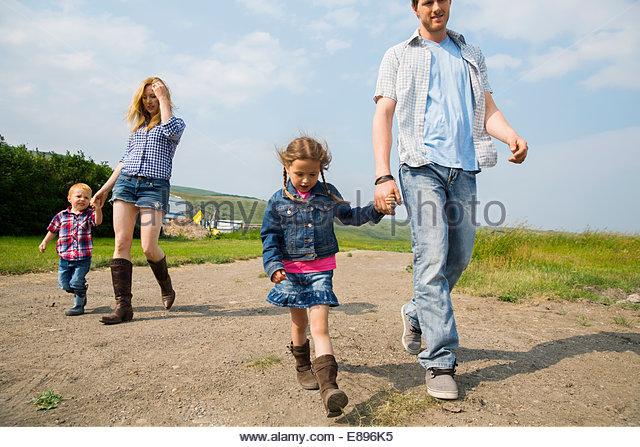 Family walking on rural dirt road - Stock Image